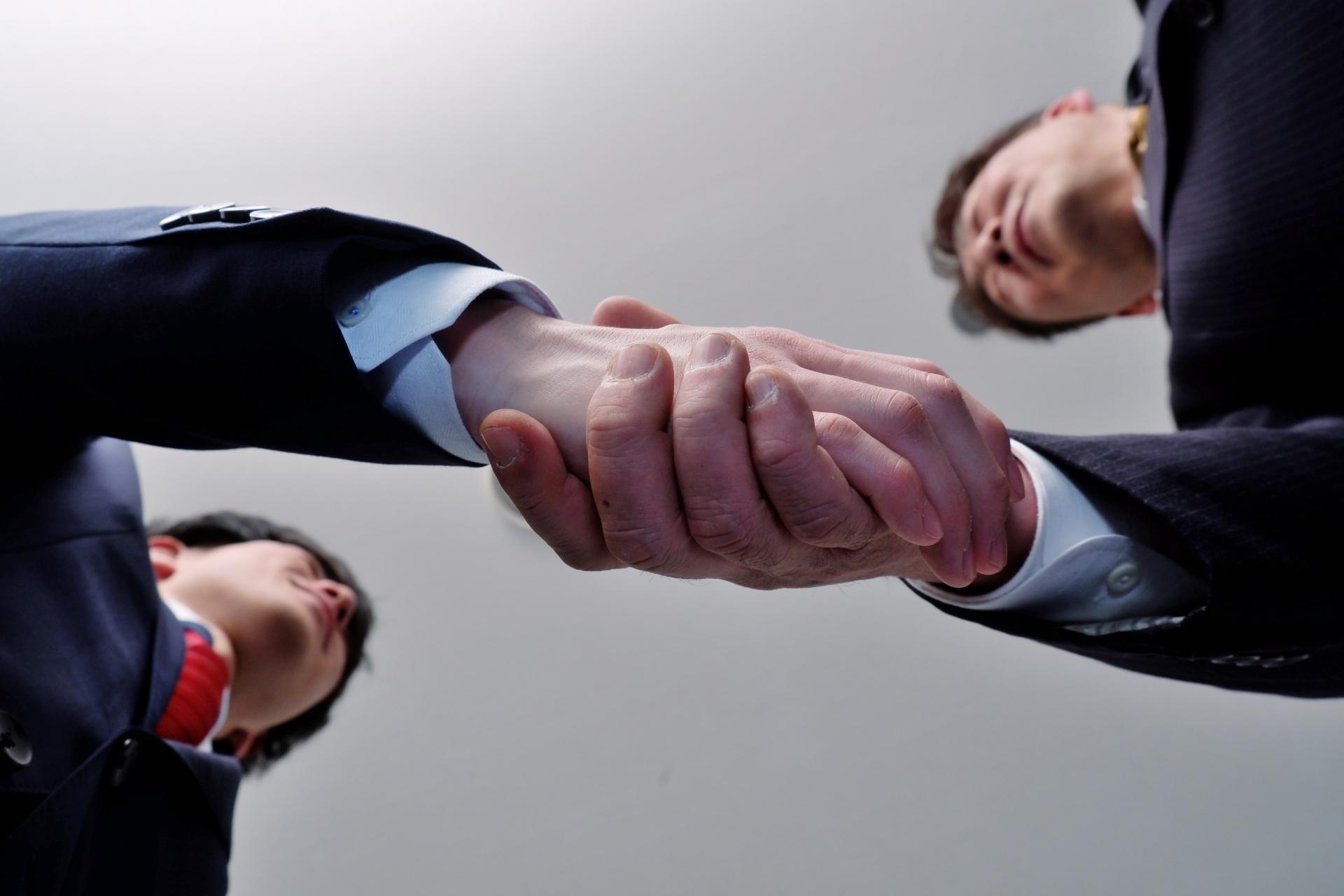 手を握り合うビジネスマン達