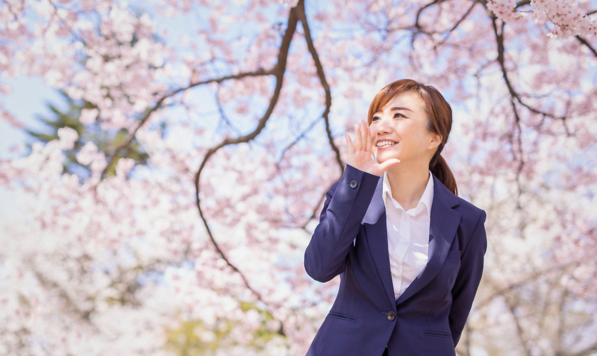 桜の下でポーズをとる女性