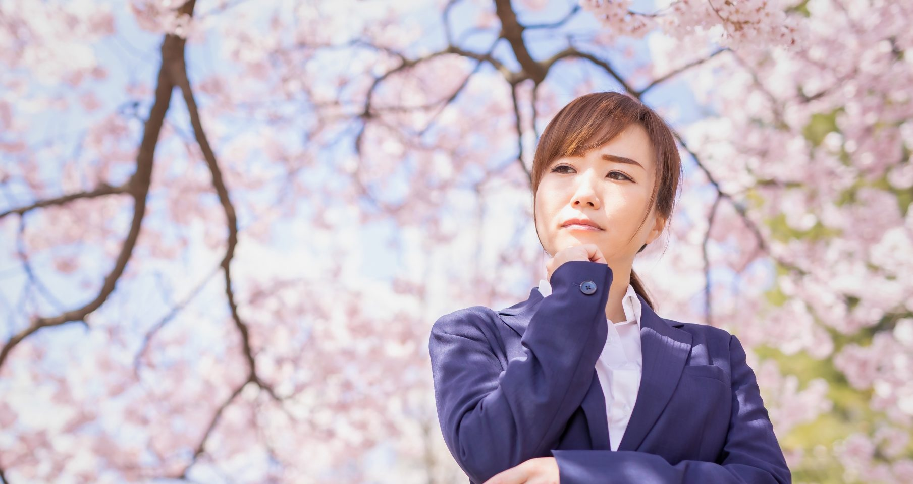 桜の下で悩む女性