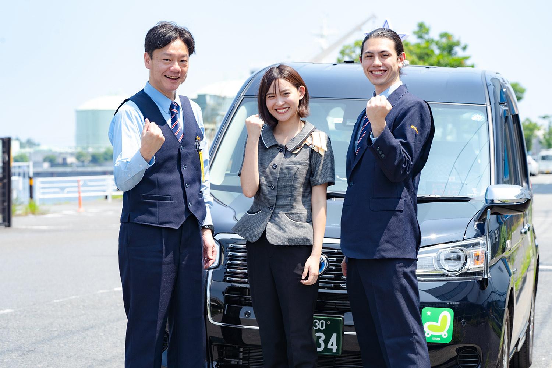 タクシー車両の前でガッツポーズをするドライバー