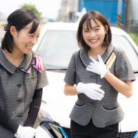 車の前で笑い合う女性二人